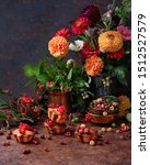 Small photo of Autumn flowers and berries on dark background. Chrysanthemums and gerberas, greenery bunch in vase botanical composition. Fresh redcurrant and gooseberries on cupcakes. Fall harvesting season concept