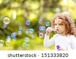 a little girl blowing soap... | Shutterstock . vector #151333820