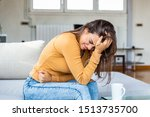 Small photo of Young sick woman with hands holding pressing her crotch lower abdomen. Medical or gynecological problems, healthcare concept. Young woman suffering from abdominal pain while sitting on sofa at home