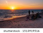 People fishing and lounging on beach chairs along the Englewood coastline in Englewood, Florida at sunset.