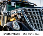 Big rig classic American idol black industrial semi truck with chrome grille and commercial cargo in dry van semi trailer standing on the truck stop parking lot at twilight time reflection sunlight - stock photo
