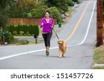 Stock photo woman running with her golden retriever dog 151457726