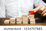 Small photo of A man is building a ladder or growth chart from blocks. Strategy planning business expansion. Climbing the career ladder. Increase in income, organization of processors. Prioritization. Leadership