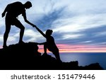 Couple hiking help teamwork and trust silhouette in mountains, sunset and ocean. Male and woman hiker helping each other on top mountain looking at beautiful night landscape motivation and inspiration
