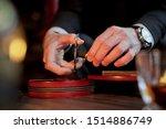 Men\'s Hands Cut A Cigar With...