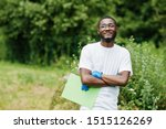 Small photo of African volunteer man with clipboard in park. Africa volunteering, charity, people and ecology concept.
