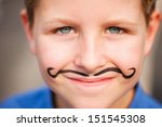 Portrait of a cute little boy with mustache painted on his face - stock photo