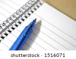 Small photo of A view from above of a spiral white lined notepad and blue pen