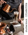 Small photo of Professional barista preparing coffee using chemex pour over coffee maker and drip kettle. Alternative ways of brewing coffee. Coffee shop concept.