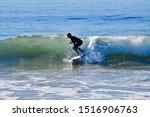 Surfer In Wet Suit Racing The...