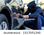 Small photo of Bully in black stocking on face and hood is scratching automobile with nail. Bandit is spoiling appearance of private car. Man is making scratch on auto without signaling. Vandalism act concept.