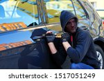Man thief in black stocking on face and hood is trying to break into automobile without signaling. Burglar is hacking door lock of private vehicle. Theft in car concept. Bad parking security. - stock photo