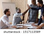 Small photo of Happy african american male manager sitting at table on business team brainstorming meeting, giving high five to arabian colleague, congratulating with shared teamwork success or good project idea.
