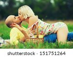 True romance concept. Weekend picnic. Portrait of a young loving couple in trendy casual clothes lying on green grass and kissing. Sunny summer (autumn) day. Copy-space. Outdoor shot - stock photo