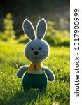 Stock photo handmade knitted toy hare amigurumi rabbit on the nature background funny hare in green pants 1517900999