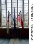 Small photo of Plymouth England September 2019. Interior view. Flags. Red white and blue ensign tied together and set against a leaded window. Explanatory text detailing what branch of the navy each flag represents.