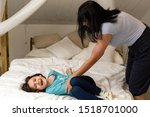 Small photo of Mom and daughter playing ticklish on the bed. Fun time with family. Bonding with mother concept