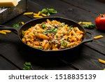Small photo of Italian pasta skillet dish. This quick & delicious pasta meal is made with penne pasta, fresh tomato sauce and sausage. This italian inspired comfort food is cooked and served in a cast iron skillet.