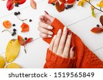 Autumn manicure. Beautyful nails design with autumn leaves. Top view. cozy autumn image. Cozy nails design. autumn leaves. Manicured woman