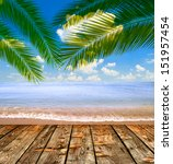 Tropical sea and beach with palm leaves and wooden floor - stock photo