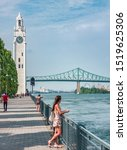 Small photo of Montreal Old Port harbour woman walking on city street looking at view of St. Lawrence River with Jacques Cartier Bridge and Tour de l'Horloge on summer day. People tourist lifestyle.