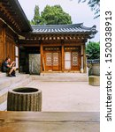 Small photo of SEPT. 19, 2019-SEOUL, SOUTH KOREA : Structure In Changgyeonggung Palace. Seoul, South Korea. A gentlemen sitting on the stoop watching on his mobile phone.