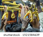 Small photo of Standing room only and closeup of passengers hands gripping straps and railings on a full, hot early evening bus from central Mysuru (formerly Mysore) bus station to nearer the outskirts of the city.