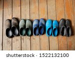 Small photo of Five pairs of old family rubber boots stand on the wooden floor. Short rubber country goloshes. Big family