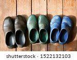 Small photo of Three pairs of old family rubber boots stand on the wooden floor. Short rubber country goloshes
