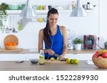 Stock photo shot of sporty young woman cutting limes while listening to music in the kitchen at home 1522289930