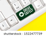 Small photo of Writing note showing Drive Safely. Business photo showcasing you should follow the rules of the road and abide laws White pc keyboard with note paper above the white background.