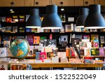 Small photo of Chiang Mai/ Thailand - August 27, 2019: Inside a bookshop with black metal electric lamps hanging and a model globe on wooden table. Lots of books displayed.