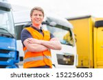 Logistics - proud driver or forwarder in front of trucks and trailers, on a transshipment point - stock photo