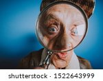 Small photo of Funny portraits with old grandmother. Senior woman acting as an investigator with the magnifying lense
