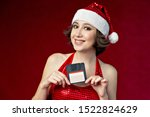 Small photo of Young woman in santa costume on a red background holding a diskette with a perplexed face. So-so gift outdated technology.