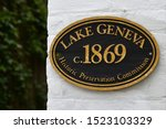 Oval Lake Geneva Historic Preservation Commission circa 1869 sign in black and gold hanging on a white brick building with green bushes in the background