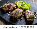 Stock photo marinated herring fillets on slices of bread on black stone 1523242520
