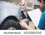 Small photo of Insurance agent working during on site car accident claim process - people and car insurance claim concept