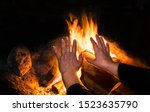 Small photo of Blazing bonfire and old lonely woman in detail on night black background. Female hands with fingers splayed over warm fire with orange burning flames. Tranquil scene of evening rest. Selective focus.