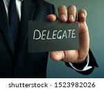 Small photo of Delegate sign in the hands of a businessman. Delegation concept.
