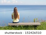 Young Woman Sitting On Bench...