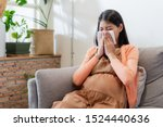 Small photo of Young Asian pregnant woman have suffering from flu and sneeze, runny nose, stuffy nose and then her blowing nose using a tissue