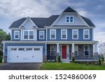 Small photo of Luxury American colonial traditional home w/ two car garage, covered porch, pacific blue horizontal vinyl and sterling gray shingle siding, fiber cement shingle gable roof, window trim, stone cladding