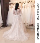 Small photo of bride chooses wedding dress in wedding dress shop