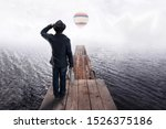 Back view of a man in black hat, standing on wooden pier and looking into the distance at paper boats and colorful air balloon. Concept of dreams and imagination. - stock photo