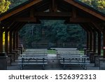 Reflective picnic tables under shelter by lake in county park, early morning in autumn, southern Wisconsin, USA