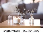 decoration, hygge and aromatherapy concept - aroma reed diffuser, burning candle, branches of eucalyptus populus and perfume on table at home