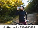 Female Cyclist Drinking Water...