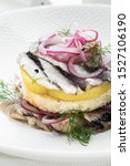 Stock photo appetizer food salted herring butter and red onion on white plate selective focus vertical view 1527106190