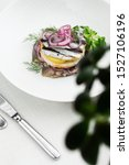 Stock photo appetizer food salted herring butter and red onion on white plate selective focus vertical view 1527106196